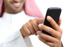 Arabisk hand för saudieremiratman som smsar i en smart telefon arkivfoton