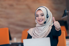 Arabisk kvinna för härlig telefonoperatör som arbetar i startup kontor Royaltyfri Bild