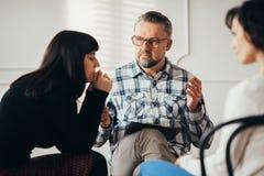 Arabisk kvinna som lyssnar till hennes psykoterapeut under stödgruppen för missbruköverlevandemöte royaltyfri fotografi