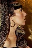 Arabisk kvinnabrunett i etnisk tillbehör, sjalhijab Guld- smink arkivbild