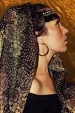 Arabisk kvinnabrunett i etnisk tillbehör, sjalhijab Guld- smink arkivfoton