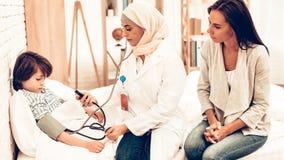 Arabisk kvinnlig pojke för doktor Checking Blood Pressure royaltyfri foto