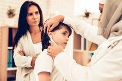 Arabisk kvinnlig pojke för doktor Examining lite royaltyfria bilder