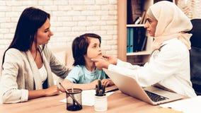 Arabisk kvinnlig pojke för doktor Examining lite royaltyfri bild