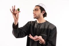 Arabisk man i etniska klänningblickar på ädelstenar royaltyfri foto