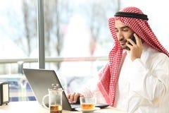 Arabisk man som använder en bärbar dator och talar på telefonen i en stång royaltyfri foto