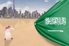 Arabisk man som drar den arabiska flaggan Arkivfoton