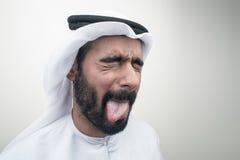 Arabisk man som ut klibbar hans tunga, arabisk grabb med rolig expr Fotografering för Bildbyråer
