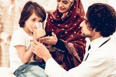 Arabisk manlig doktor Give Medicine till den sjuka pojken royaltyfri fotografi