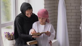 Arabisk moder och son som inomhus läser arkivbilder