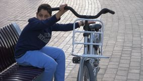 Arabisk pojke med cykelsammanträde på bänk på den Dubai marina lager videofilmer