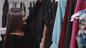 Arabiska kvinnor för nätt brunett som shoppar i detaljist Flickan väljer klänningen i galleria arkivfilmer