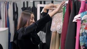 Arabiska kvinnor för nätt brunett som shoppar i detaljist Flickan väljer klänningen i galleria lager videofilmer