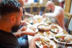Arabiska män i restaurang som tycker om mitt - östlig mat fotografering för bildbyråer