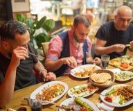 Arabiska män i restaurang som tycker om mitt - östlig mat royaltyfri foto