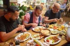 Arabiska män i restaurang som tycker om mitt - östlig mat arkivfoton