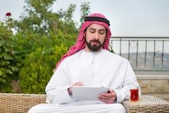 Arabiskt manarbete på en mobil tablet & en dricka tea royaltyfri fotografi