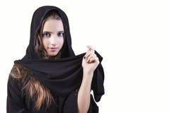 Arabiskt muslim, flickacloseup på en vit bakgrund Arabisk framsida för saudieremiratkvinna som ser sidan som isoleras på en vit b royaltyfri bild