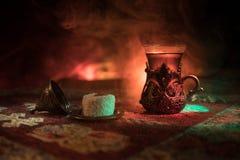 Arabiskt te i exponeringsglas med östliga mellanmål på en matta på mörk bakgrund med ljus och rök Östligt tebegrepp Töm utrymme royaltyfri bild