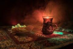 Arabiskt te i exponeringsglas med östliga mellanmål på en matta på mörk bakgrund med ljus och rök Östligt tebegrepp Töm utrymme arkivbilder