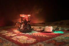 Arabiskt te i exponeringsglas med östliga mellanmål på en matta på mörk bakgrund med ljus och rök Östligt tebegrepp Töm utrymme royaltyfria foton