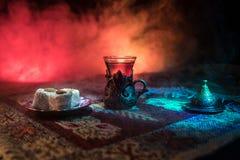 Arabiskt te i exponeringsglas med östliga mellanmål på en matta på mörk bakgrund med ljus och rök Östligt tebegrepp Töm utrymme arkivfoton