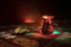 Arabiskt te i exponeringsglas med östliga mellanmål på en matta på mörk bakgrund med ljus och rök Östligt tebegrepp Töm utrymme arkivfoto