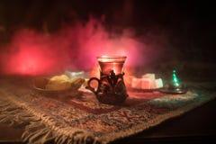 Arabiskt te i exponeringsglas med östliga mellanmål på en matta på mörk bakgrund med ljus och rök Östligt tebegrepp Töm utrymme royaltyfria bilder