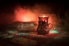 Arabiskt te i exponeringsglas med östliga mellanmål på en matta på mörk bakgrund med ljus och rök Östligt tebegrepp Töm utrymme arkivbild