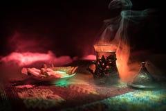 Arabiskt te i exponeringsglas med östliga mellanmål på en matta på mörk bakgrund med ljus och rök Östligt tebegrepp Töm utrymme royaltyfri foto