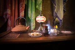Arabiskt te i exponeringsglas med östliga mellanmål på tappningträyttersida Östligt tebegrepp Låg ljus vardagsrum som är inre med fotografering för bildbyråer