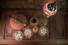 Arabiskt te i exponeringsglas med östliga mellanmål på tappningträyttersida Östligt tebegrepp Låg ljus vardagsrum som är inre med royaltyfria foton