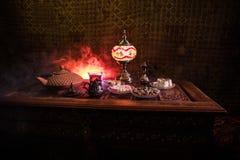 Arabiskt te i exponeringsglas med östliga mellanmål på tappningträyttersida Östligt tebegrepp Låg ljus vardagsrum som är inre med arkivbild