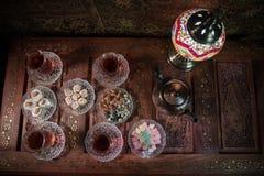 Arabiskt te i exponeringsglas med östliga mellanmål på tappningträyttersida Östligt tebegrepp Låg ljus vardagsrum som är inre med royaltyfri foto
