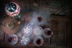 Arabiskt te i exponeringsglas med östliga mellanmål på tappningträyttersida Östligt tebegrepp Låg ljus vardagsrum som är inre med arkivbilder