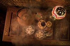 Arabiskt te i exponeringsglas med östliga mellanmål på tappningträyttersida Östligt tebegrepp Låg ljus vardagsrum som är inre med arkivfoton
