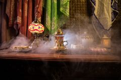 Arabiskt te i exponeringsglas med östliga mellanmål på tappningträyttersida Östligt tebegrepp Låg ljus vardagsrum som är inre med royaltyfri bild