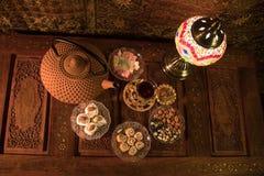Arabiskt te i exponeringsglas med östliga mellanmål på tappningträyttersida Östligt tebegrepp Låg ljus vardagsrum som är inre med royaltyfria bilder