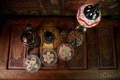 Arabiskt te i exponeringsglas med östliga mellanmål på tappningträyttersida Östligt tebegrepp Låg ljus vardagsrum som är inre med royaltyfri fotografi