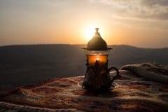 Arabiskt te i exponeringsglas på en östlig matta Östligt tebegrepp Armudu traditionell kopp baltisk havssolnedgång för bakgrund S arkivfoton