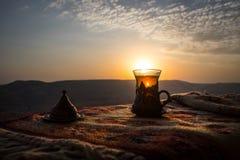 Arabiskt te i exponeringsglas på en östlig matta Östligt tebegrepp Armudu traditionell kopp baltisk havssolnedgång för bakgrund S arkivfoto