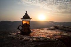 Arabiskt te i exponeringsglas på en östlig matta Östligt tebegrepp Armudu traditionell kopp baltisk havssolnedgång för bakgrund S royaltyfri fotografi