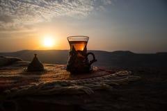 Arabiskt te i exponeringsglas på en östlig matta Östligt tebegrepp Armudu traditionell kopp baltisk havssolnedgång för bakgrund S fotografering för bildbyråer