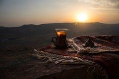 Arabiskt te i exponeringsglas på en östlig matta Östligt tebegrepp Armudu traditionell kopp baltisk havssolnedgång för bakgrund S royaltyfri foto