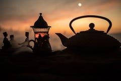 Arabiskt te i traditionell exponeringsglas och kruka på öken på solnedgången Östligt tebegrepp Konstverkgarnering på sand med te royaltyfri fotografi