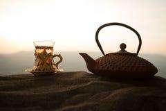 Arabiskt te i traditionell exponeringsglas och kruka på öken på solnedgången Östligt tebegrepp Konstverkgarnering på sand med te fotografering för bildbyråer