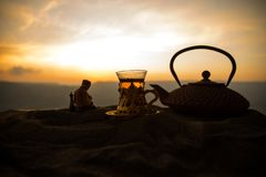 Arabiskt te i traditionell exponeringsglas och kruka på öken på solnedgången Östligt tebegrepp Konstverkgarnering på sand med te arkivfoton
