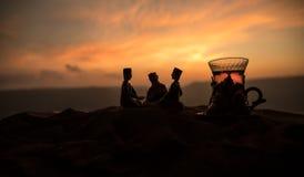 Arabiskt te i traditionell exponeringsglas och kruka på öken på solnedgången Östligt tebegrepp Konstverkgarnering på sand med te arkivbilder