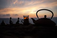 Arabiskt te i traditionell exponeringsglas och kruka på öken på solnedgången Östligt tebegrepp Konstverkgarnering på sand med te royaltyfri foto