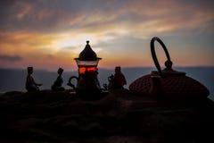 Arabiskt te i traditionell exponeringsglas och kruka på öken på solnedgången Östligt tebegrepp Konstverkgarnering på sand med te royaltyfria foton